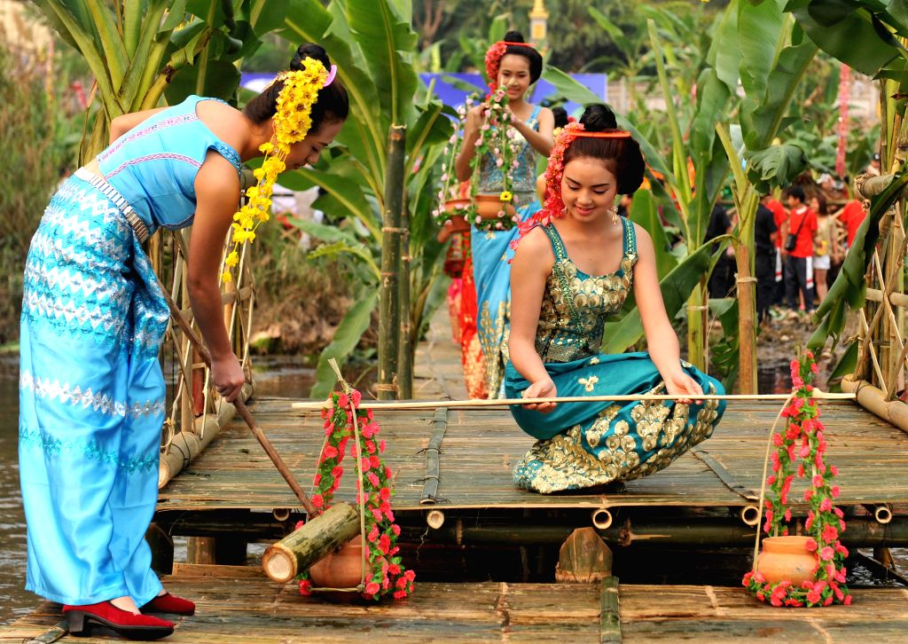 Girls of the Dai ethnic group fetch water during the Water-splashing Festival in Jinghong City of Dai Autonomous Prefecture of Xishuangbanna, southwest ...