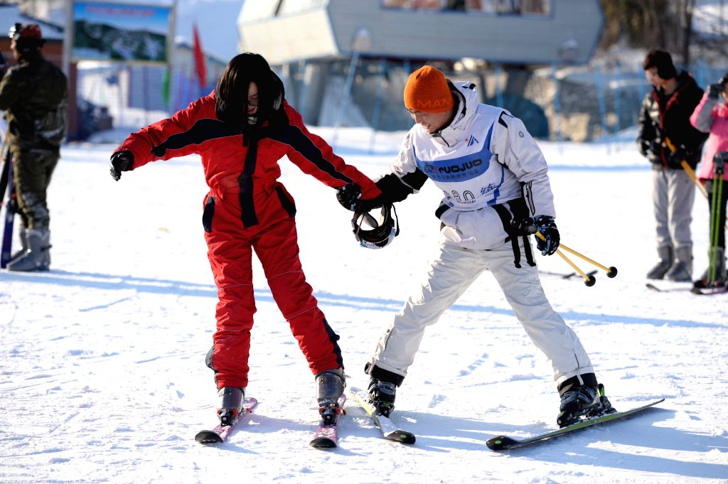 A tourist learns skiing from a coach at a ski resort in Yabuli town, northeast China's Heilongjiang Province, Jan. 22, 2015. The town has received nearly 150,000 ...