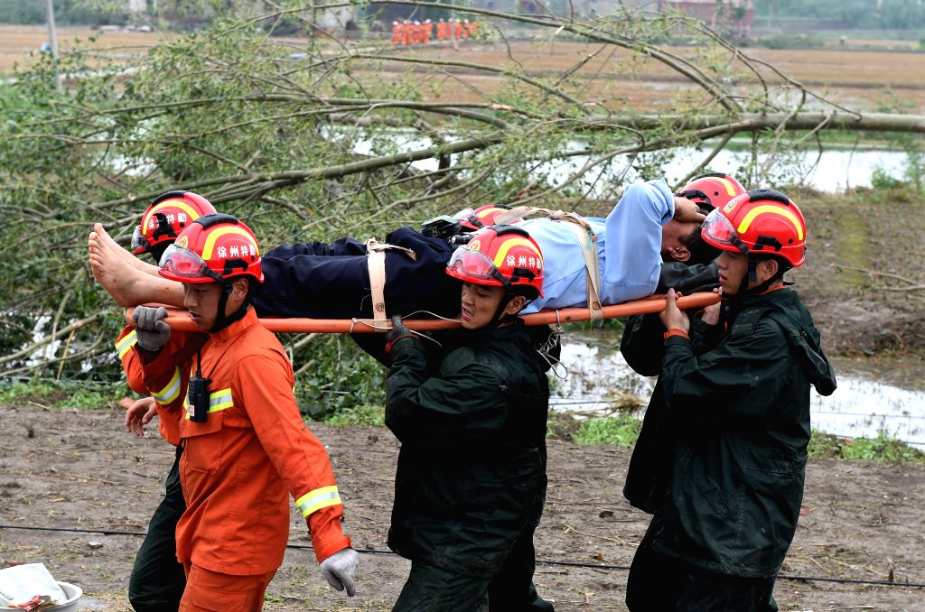 YANCHENG, June 24, 2016 - Rescuers carry an injured person with a stretcher in Danping Village of Chenliang Township in Funing County, Yancheng City, east China's Jiangsu Province, June 24, 2016. ...