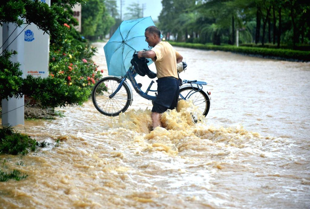 YANGJIANG, Sept. 17, 2018 - A citizen wades through a waterlogged street in Yangchun, south China's Guangdong Province, Sept. 17, 2018. A rain-triggered flood hit Yangchun due to the influence of ...