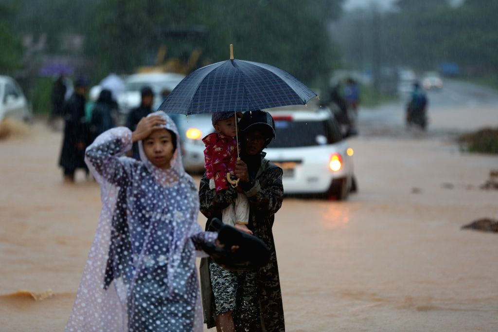 YANGON, Aug. 10, 2019 - People walk on a flooded road during monsoon rain in Paung Township, Mon state, Myanmar, Aug. 10, 2019. Death toll from Friday's monsoon landslide had risen to 29 so far in ...