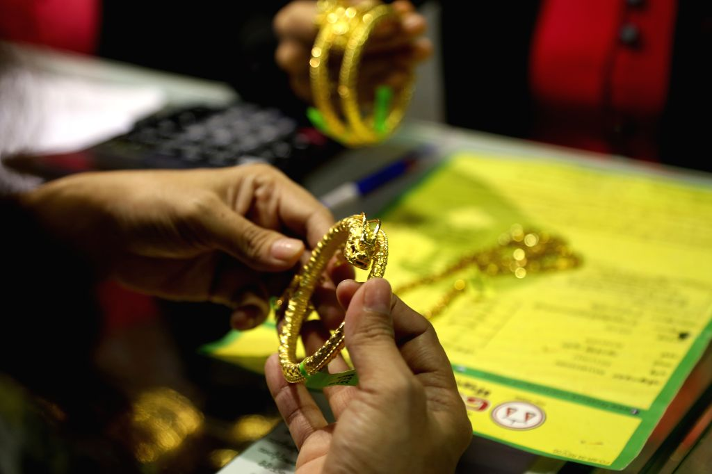 YANGON, Aug. 13, 2019 - A customer chooses gold bracelet at a jewelry shop in Yangon, Myanmar, Aug. 13, 2019. Myanmar's domestic gold price edged higher with around 1.23 million kyats (816 U.S. ...