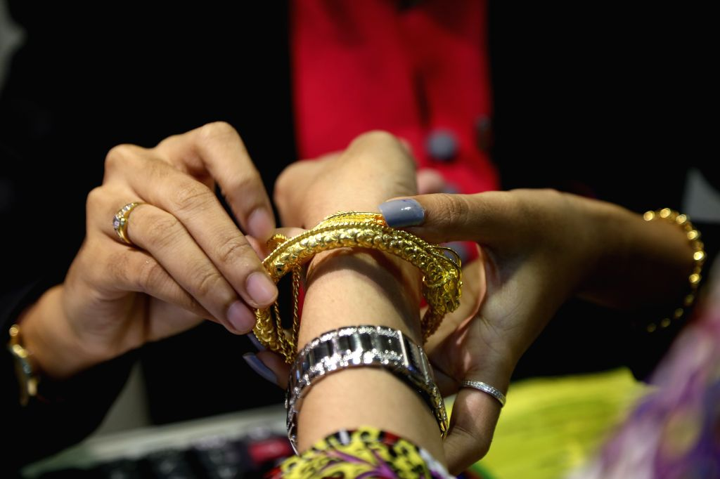 YANGON, Aug. 13, 2019 - A salesperson places a gold bracelet on the wrist of a customer at a jewelry shop in Yangon, Myanmar, Aug. 13, 2019. Myanmar's domestic gold price edged higher with around ...