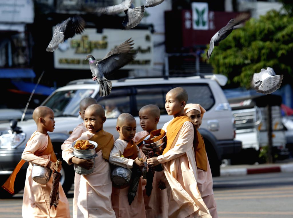 Myanmar buddhist novices walk on a road near the Sule Pagoda in downtown Yangon, Myanmar, Dec. 12, 2014. Myanmar implemented a 20-year project with four phases aimed