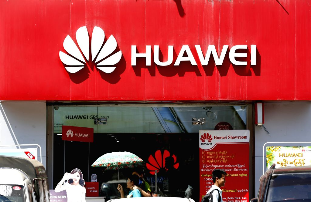 YANGON, March 12, 2017 - People walk past a store of Huawei in Yangon, Myanmar, March 12, 2017. China's investment in Myanmar reached 2.8 billion U.S. dollars in this fiscal year 2016-2017, ...