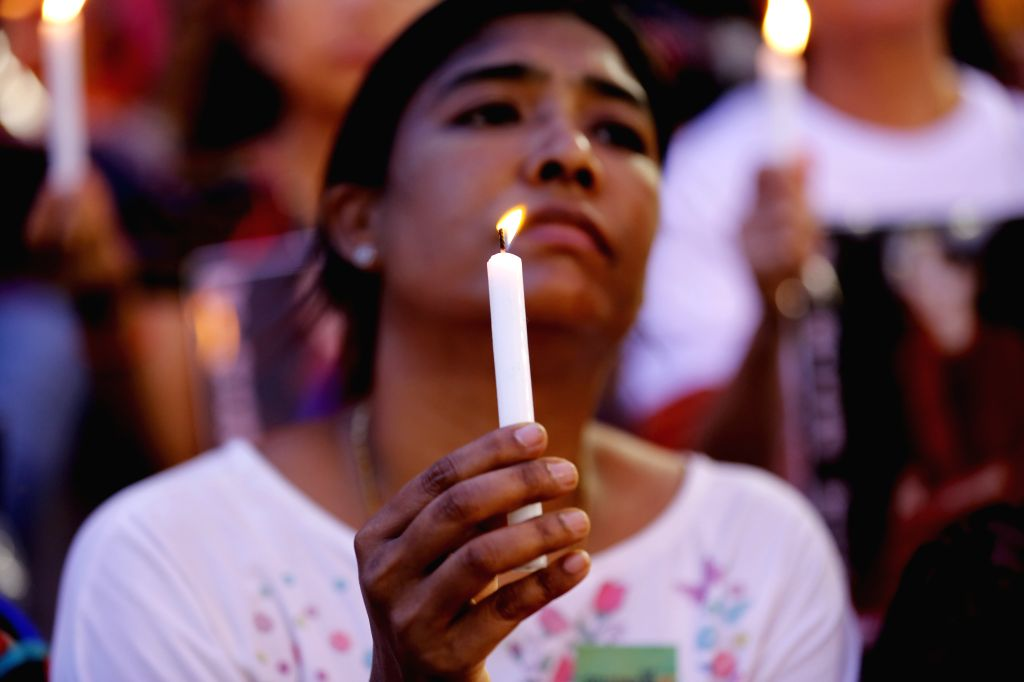 YANGON, Oct. 11, 2017 - A woman holds a candle as she prays during the inter-faith gathering of prayers for peace ceremony at the Aung San stadium in Yangon, Myanmar, Oct. 10, 2017. People with ...