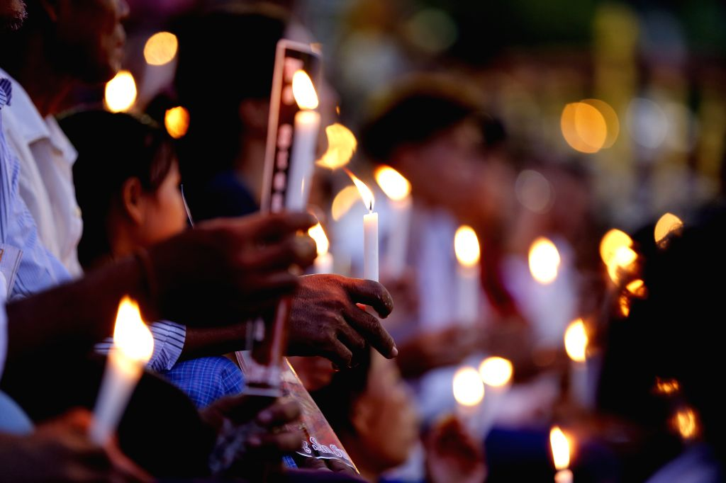 YANGON, Oct. 11, 2017 - People hold candles as they pray during the inter-faith gathering of prayers for peace ceremony at the Aung San stadium in Yangon, Myanmar, Oct. 10, 2017. People with ...