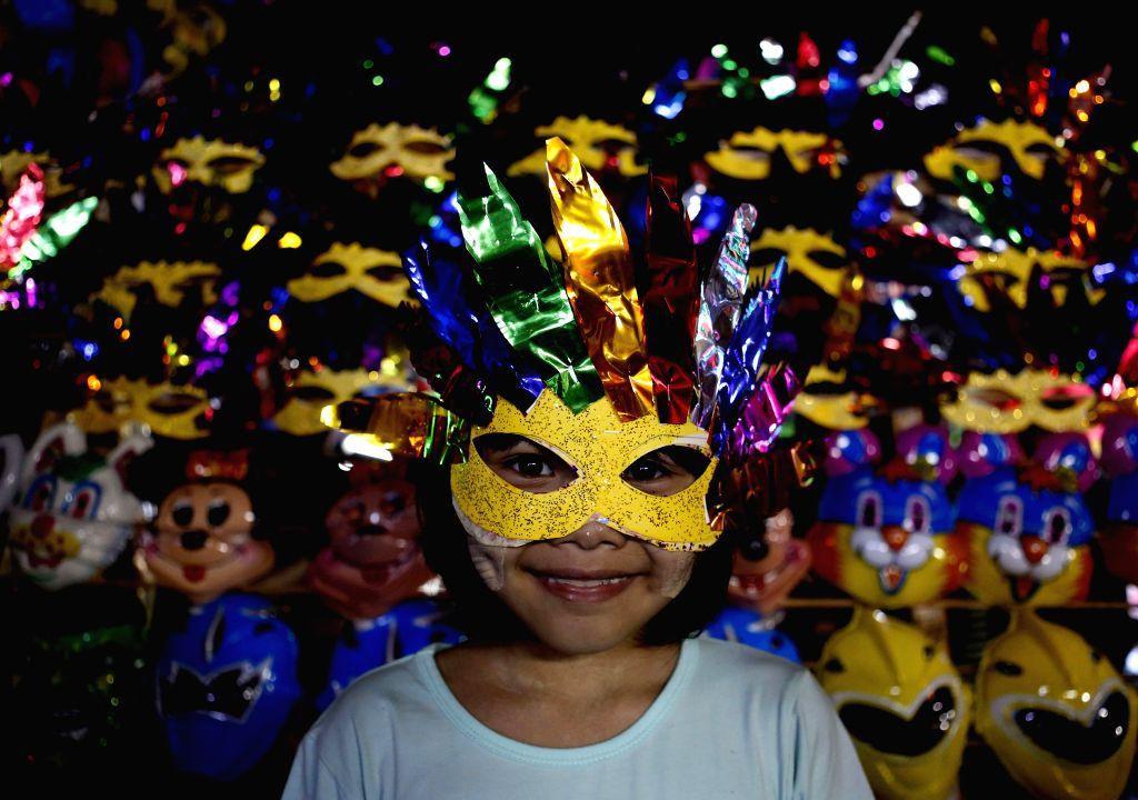 YANGON, Oct. 14, 2016 - A girl wearing a mask attends the Thadingyut Festival celebration in Yangon, Myanmar, Oct. 13, 2016. Thadingyut Festival, the Lighting Festival of Myanmar, is held on the full ...