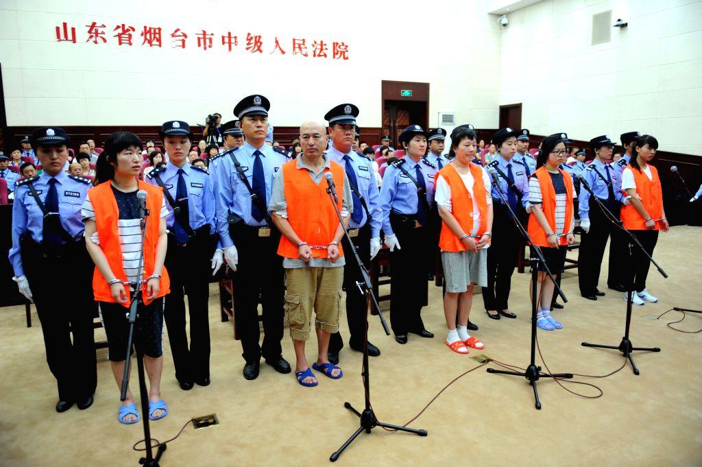Five cult members Zhang Fan, Zhang Lidong, Lyu Yingchun, Zhang Hang and Zhang Qiaolian stand trial on murder charges in Yantai Intermediate People's Court in Yantai .