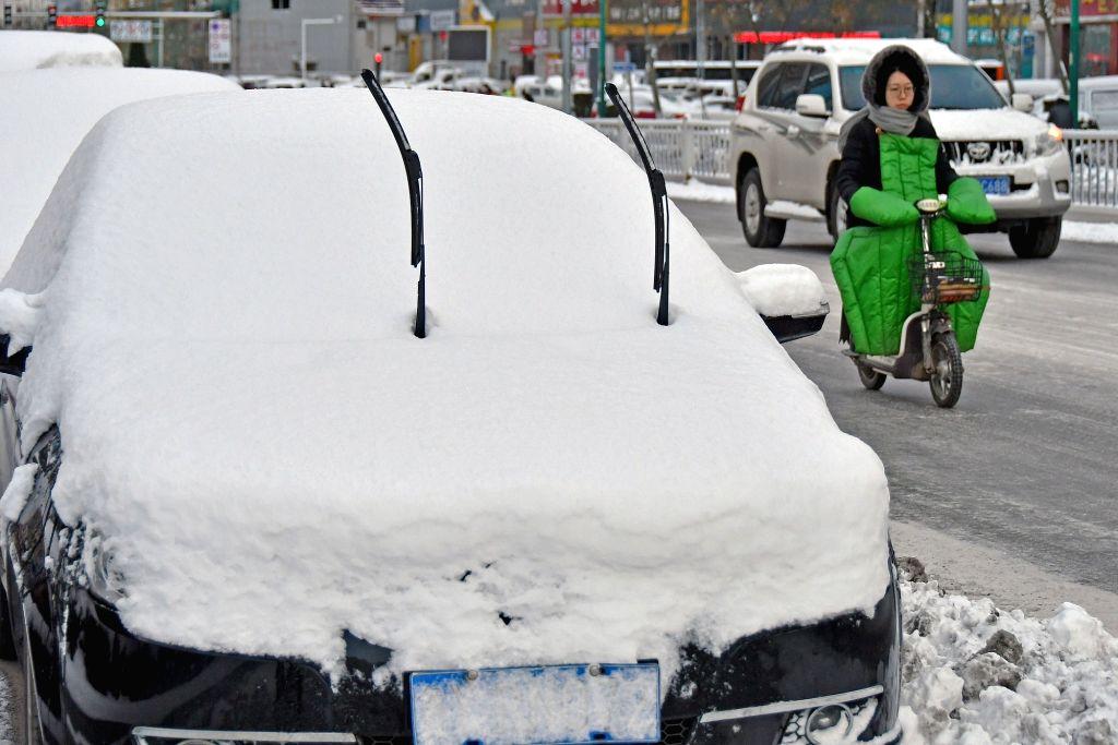 YANTAI, Dec. 7, 2018 - A woman rides electric bicycle on a street at Fushan District in Yantai City, east China's Shandong Province, Dec. 7, 2018. Snowfall and sleet hit Shandong Friday.