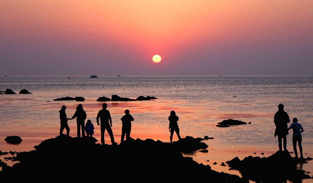 YANTAI, May 3, 2019 - Tourists watch the sunrise at a beach in Yantai, east China's Shandong Province, May 3, 2019. People across China take advantage of the four-day Labor Day national holiday to ...