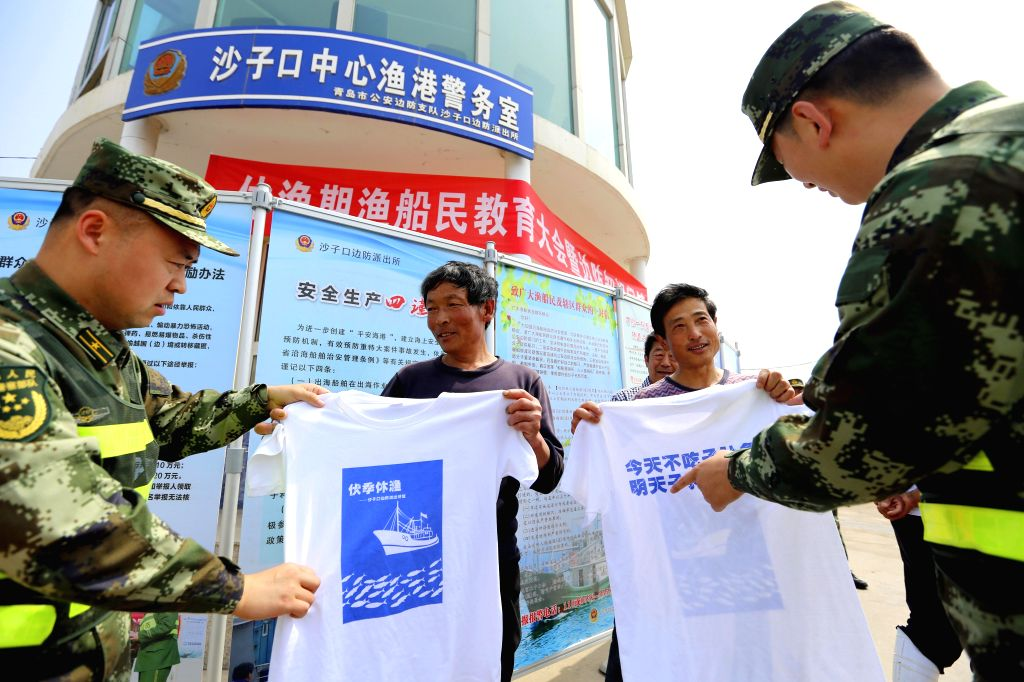 YANTAI, May 30, 2016 - Police officers send moratorium T-shirts to local fishermen at a fishing port in Qingdao, east China's Shandong Province, May 30, 2016. The summer fishing moratorium in the ...