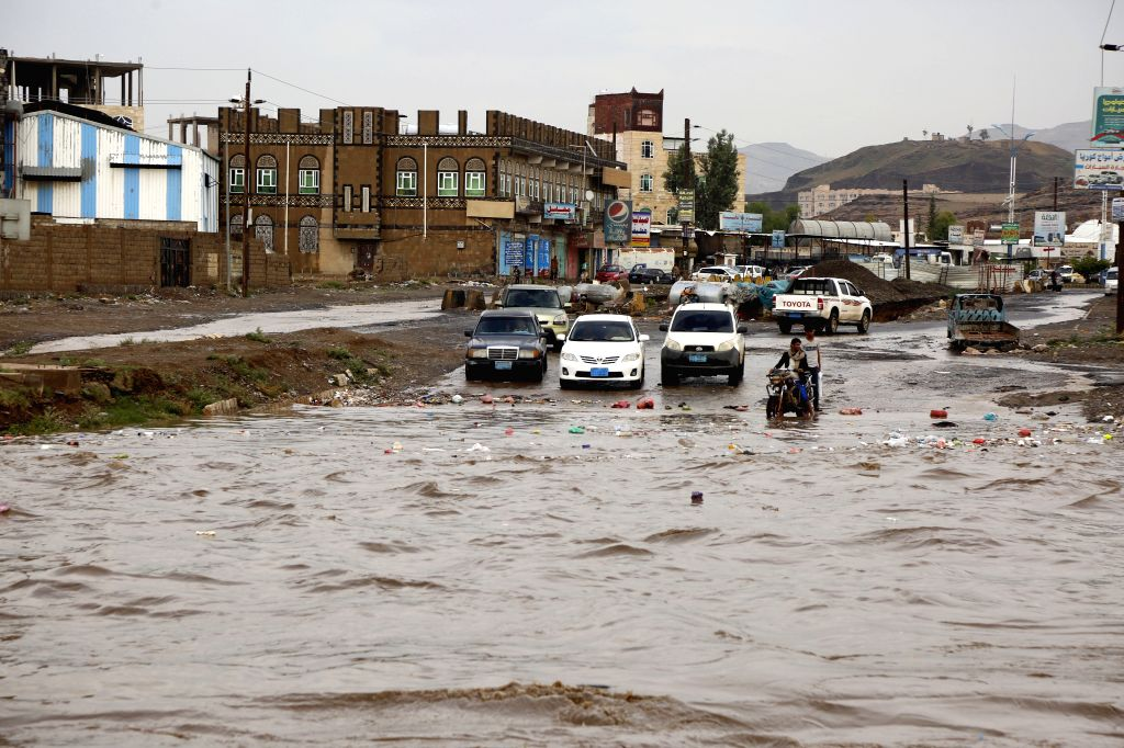 YEMEN, Aug. 10, 2019 - People wait on their cars and motorcycle by a flooded street after the heavy rain in Sanaa, Yemen, Aug. 10, 2019. Heavy rain hit Sanaa on Saturday.