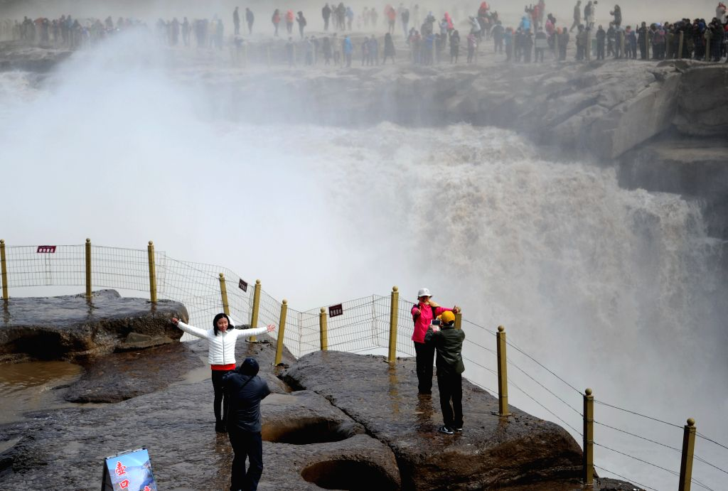 YICHUAN, April 6, 2018 - Tourists pose for photos at Hukou Waterfall of the Yellow River, which is located on the border area between north China's Shanxi and northwest China's Shaanxi provinces, ...