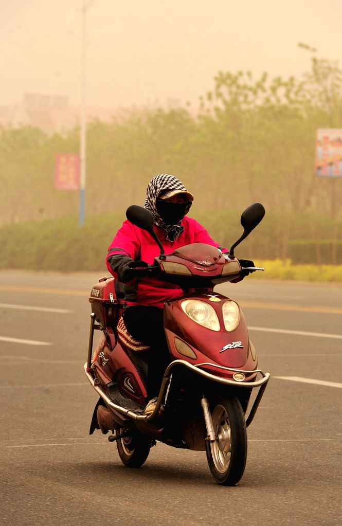 A woman rides in sandstorm in Zhongwei City, northwest China's Ningxia Hui Autonomous Region, April 24, 2014. Parts of Ningxia was hit by a sandstorm Thursday ...