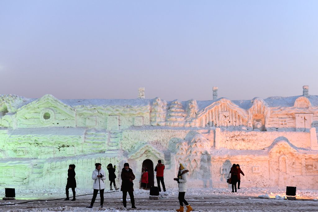 Visitors walk past snow sculptures at Hengcheng scenic spot in Yinchuan, capital of northwest China's Ningxia Hui Autonomous Region, Jan. 10, 2015. An ice and snow