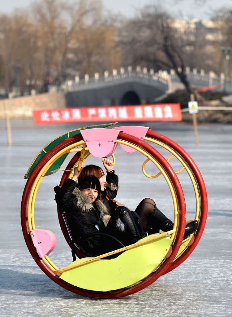 Citizens have fun on ice at the Zhongshan Park in Yinchuan, capital city of northwest China's Ningxia Hui Autonomous Region, Jan. 25, 2015.    .