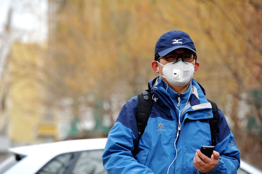 A man wearing a mask walks amid floating dust and sand in Wuzhong City, northwest China's Ningxia Hui Autonomous Region, March 2, 2015. The region's weather ...