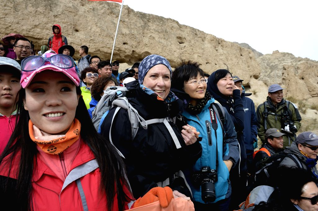 Sylvia poses for photo with travellers at the foot of the Sanguankou Great Wall of Ming Dynasty (1368-1644) in northwest China's Ningxia Hui Autonomous Region, May .