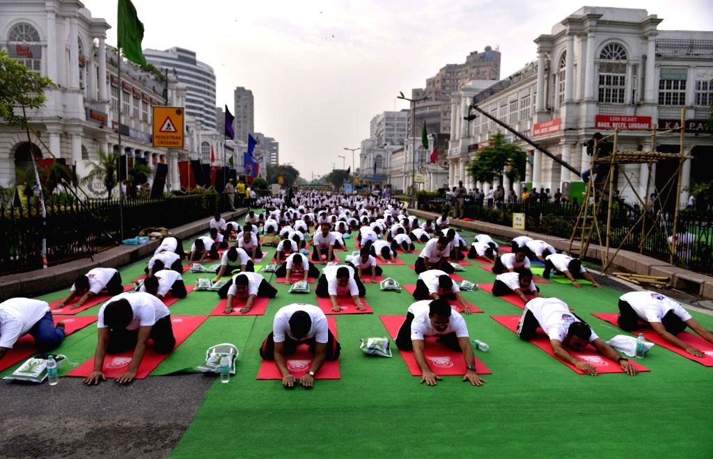 Yoga enthusiasts practice Yoga Asans  -postures- on International Yoga Day at Connaught Place in New Delhi on June 21, 2017.