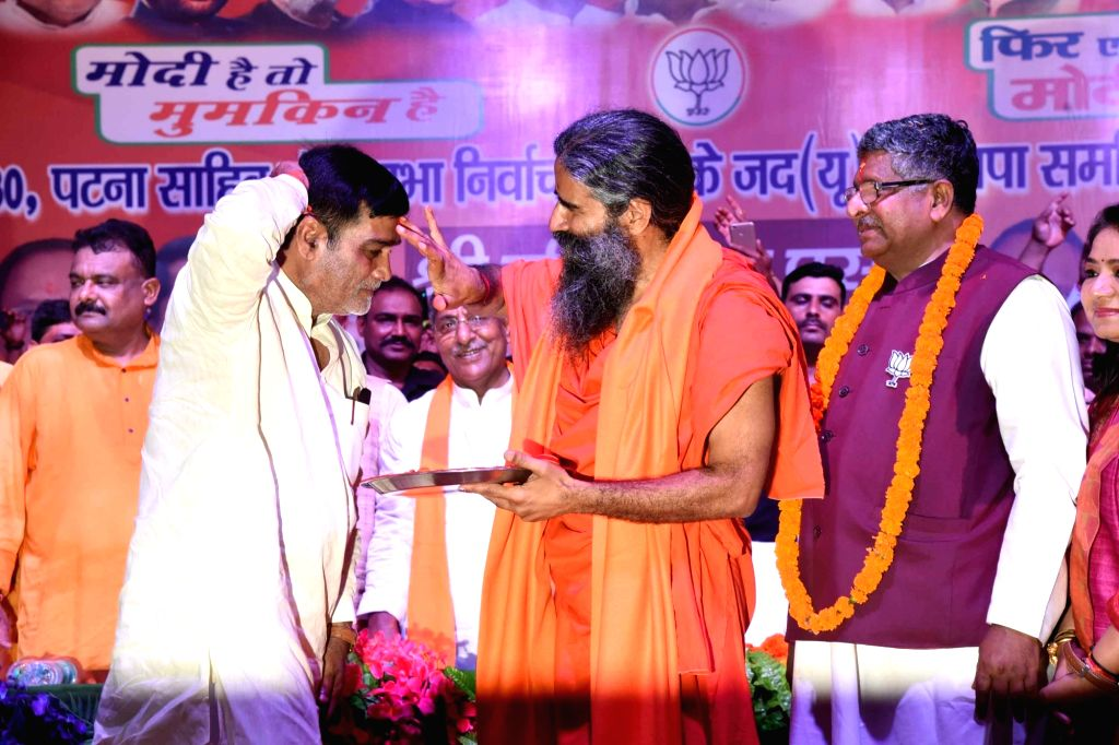 Yoga Guru Baba Ramdev applies 'tilak' on the forehead of BJP's Lok Sabha candidate from Pataliputra, Ram Kripal Yadav during a public rally, in Patna, on April 26, 2019. Also seen BJP's Lok ... - Kripal Yadav