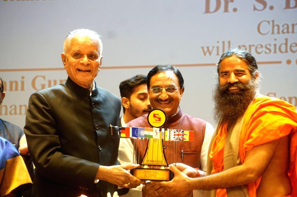 Yoga Guru Baba Ramdev being felicitated by Symbiosis International University Chancellor S. B. Mujumdar during the inauguration of the University's Noida campus, on Sep 24, 2019. Also seen ... - Ramesh Pokhriyal