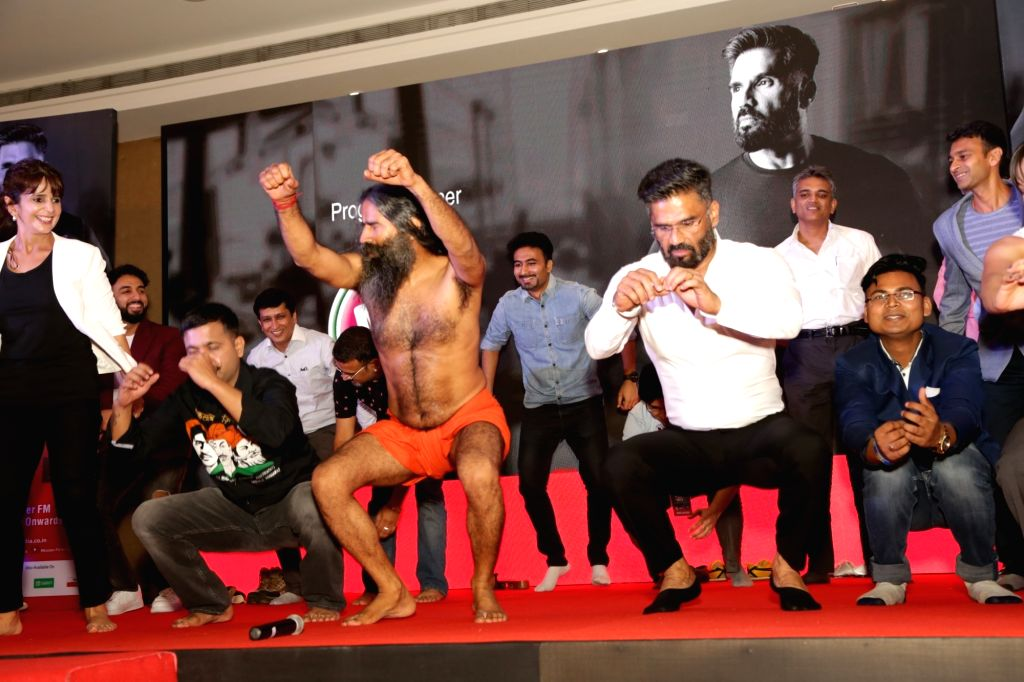 """Yoga guru Ramdev and actor Suniel Shetty demonstrate yoga during a press conference organised to launch """"Mission Fit India"""" in New Delhi, on June 4, 2018. - Suniel Shetty"""