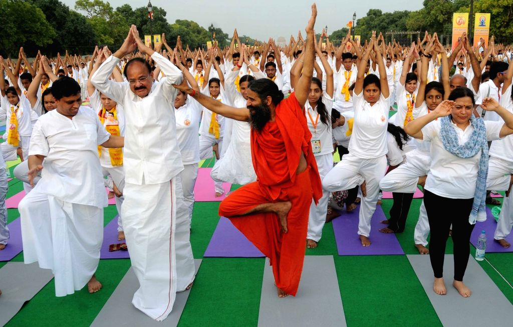 Yoga Guru Ramdev corrects posture of yoga to Union Minister for Urban Development, Housing and Urban Poverty Alleviation and Parliamentary Affairs M Venkaiah Naidu during a Yoga programme ... - Venkaiah Naidu