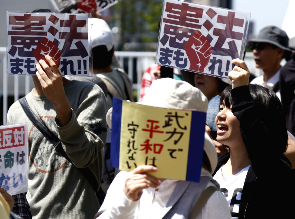 People attend a demonstration for the protection of the Japan's pacifist Constitution in Yokohama, Japan, May 3, 2015. Some hundreds of people participated in the ...