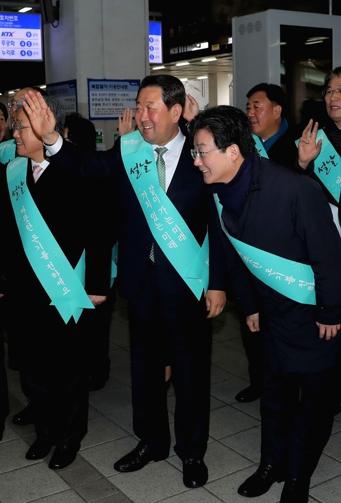 Yoo Seong-min (R) and Park Joo-sun (C), co-leaders of the new 30-seat Bareun Future Party, send off homebound passengers at Seoul's Yongsan Station on Feb. 14, 2018, as South Korea's annual ...