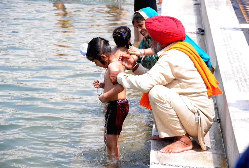 Young devotees being given a holy dip in the pond at Golden Temple on the occasion of the birth anniversary of fifth Sikh master Sri Guru Arjan Dev Ji, in Amritsar on April 7, 2018.