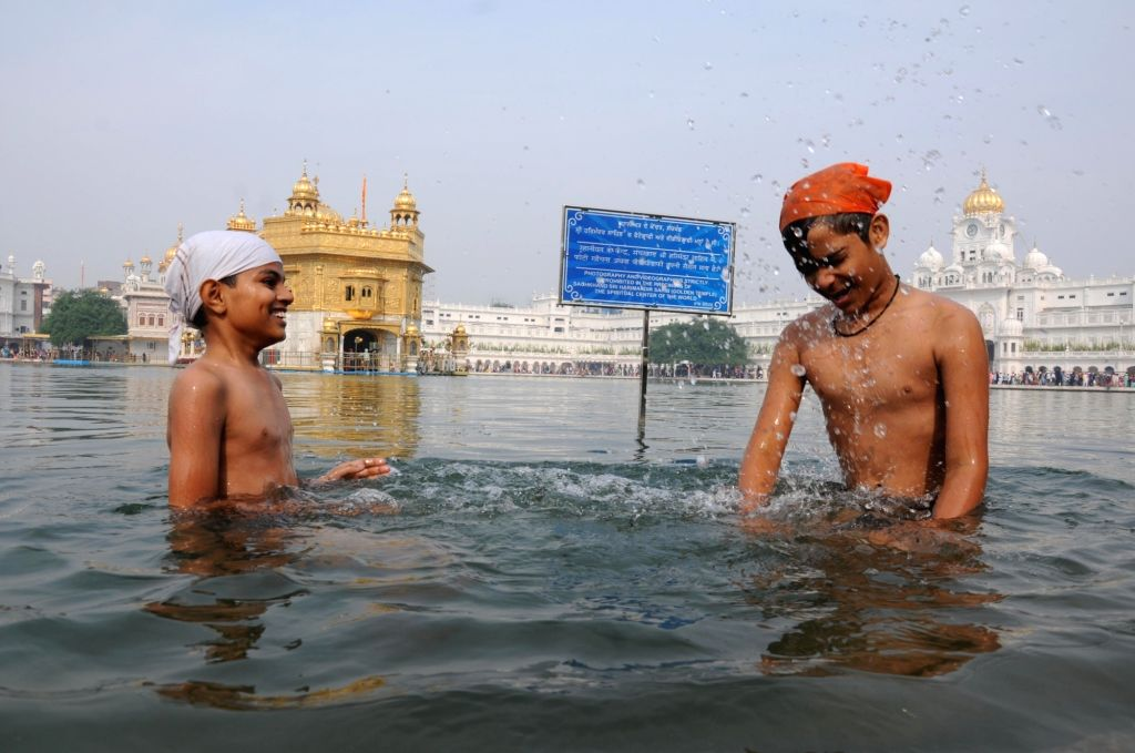 Young devotees take a dip in the holy pond at the Golden Temple during the 550th birth anniversary celebrations of Guru Nanak Dev in Amritsar on Nov 12, 2019. - Nanak Dev