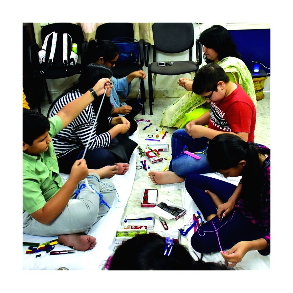 Young hands learning the art of making seed rakhi.