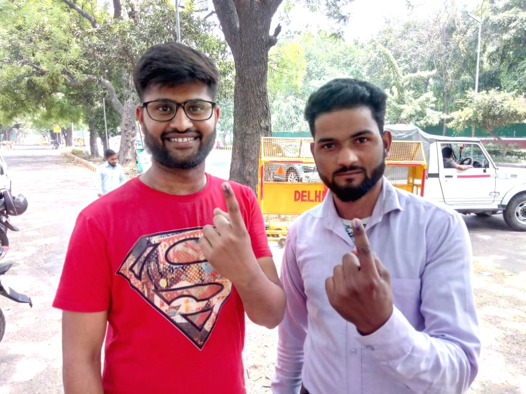 Young voters show their forefinger marked with indelible ink after casting vote during the sixth phase of 2019 Lok Sabha polls, in New Delhi, on May 12, 2019.