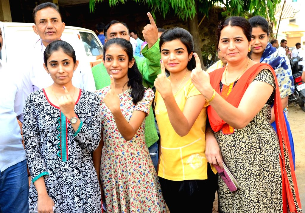 Young voters show their inked finger after casting vote for Lok Sabha election at a polling station, in Nagpur, on April 11, 2019.