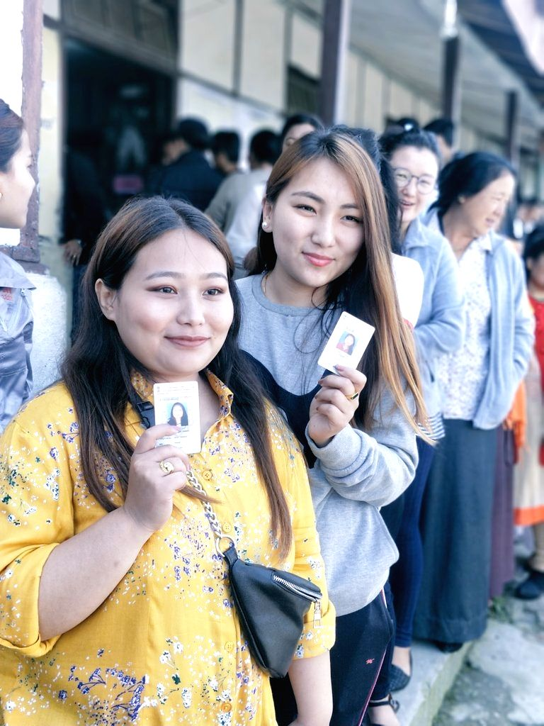 Young voters wait in queue to cast vote for Lok Sabha election at a polling station, in Gangtok, Sikkim, on April 11, 2019.