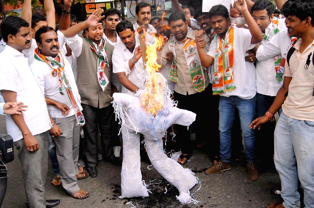 Youth Congress workers burn effigies of Prime Minister Narendra Modi as they demonstrate against hike in fuel prices and rail tariff in Bangalore on July 15, 2014. - Narendra Modi