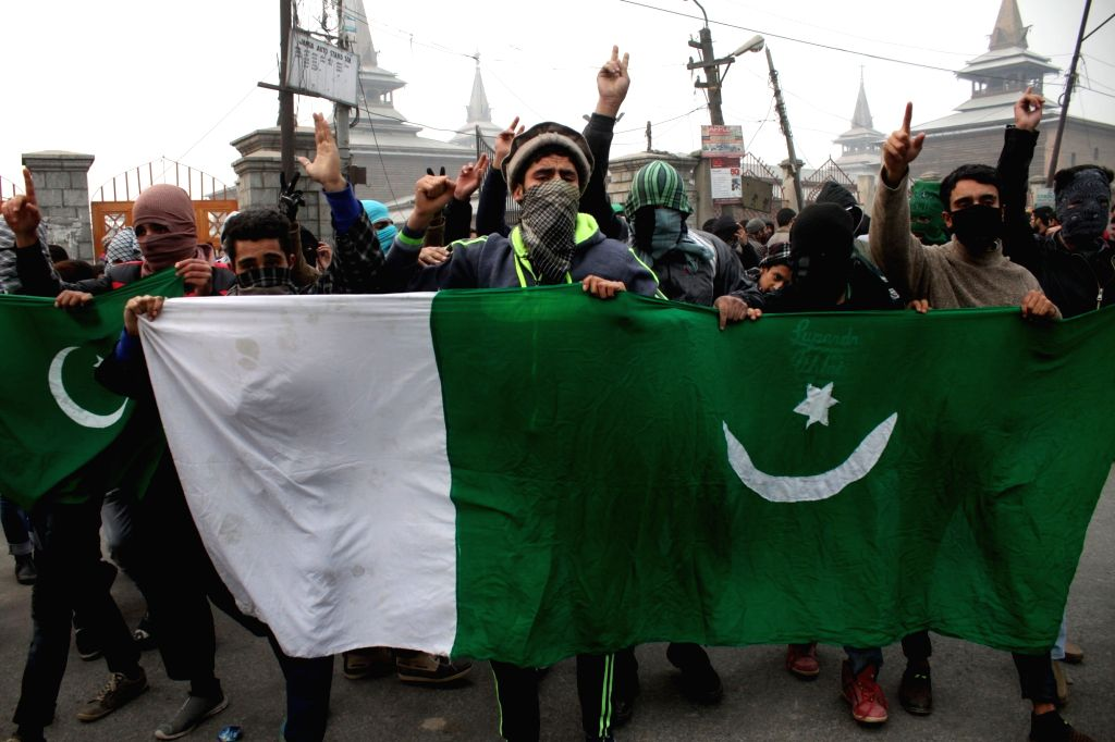 Youths holding Pakistan flags stage a demonstration outside Jama Masjid in Srinagar on Nov 25, 2016. Friday prayers were offered in the historic Jamia Masjid after 19 weeks since the ...