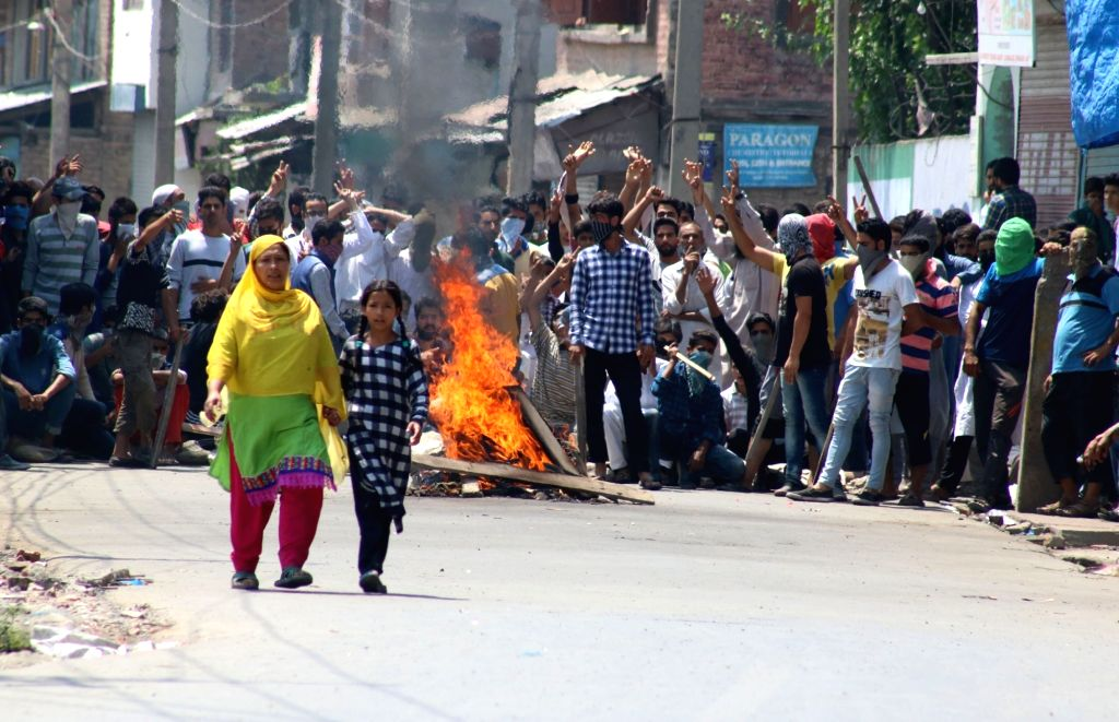 Youths protest as curfew continues in Srinagar on July 23, 2016.