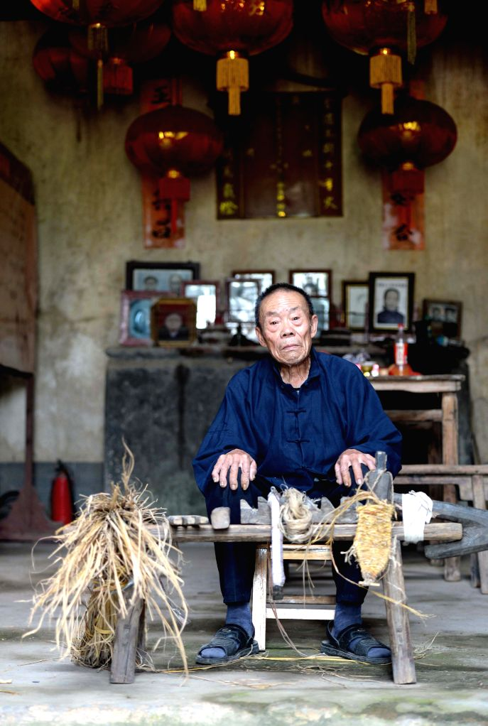 Straw sandal craftsman Chen Luoshou poses for photos with his straw sandals weaving tools in Buqian Village of Luoao Township in Yudu County, east China's Jiangxi ...