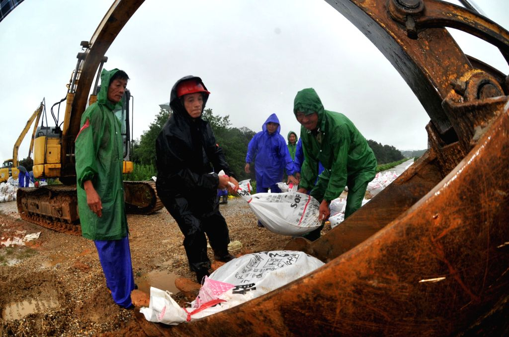 YUEYANG, July 5, 2016 - Workers carry sandbags on a dyke in Yunxi District of Yueyang, central China's Hunan Province, July 5, 2016. Continuous rainfall has affected 522,300 people, destroyed 600 ...