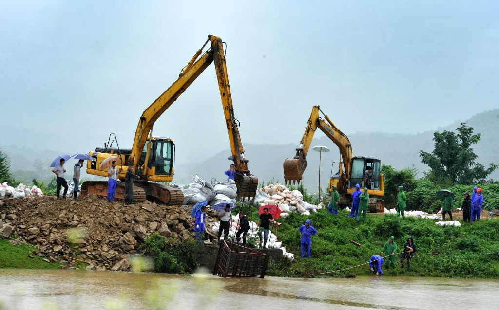 YUEYANG, July 5, 2016 - Workers reinforce a dyke in Yunxi District of Yueyang, central China's Hunan Province, July 5, 2016. Continuous rainfall has affected 522,300 people, destroyed 600 houses and ...