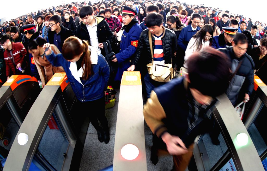 Passengers queue to board trains at Yuncheng North Railway Station in Yuncheng, north China's Shanxi Province, March 6, 2015. The railway stations around the ...