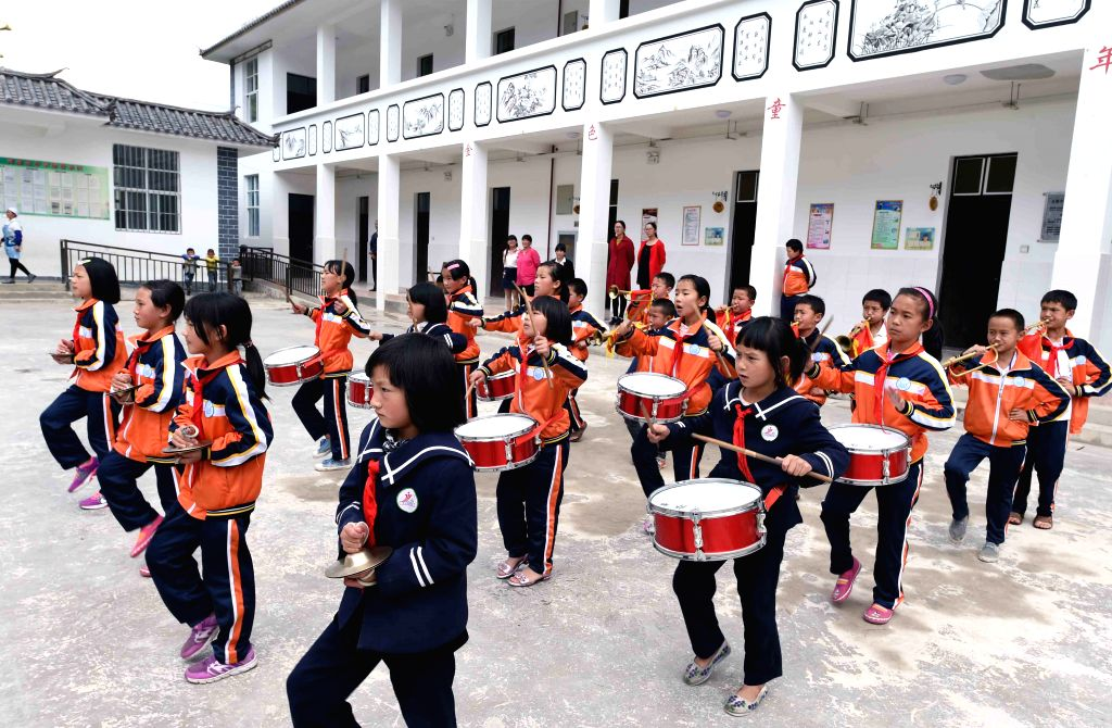 YUNLONG, May 25, 2017 - Pupils play musical instruments at Henan Primary School in Tuanjie Township of Yi ethnic group in Yunlong County, southwest China's Yunnan Province, May 19, 2017. The primary ...