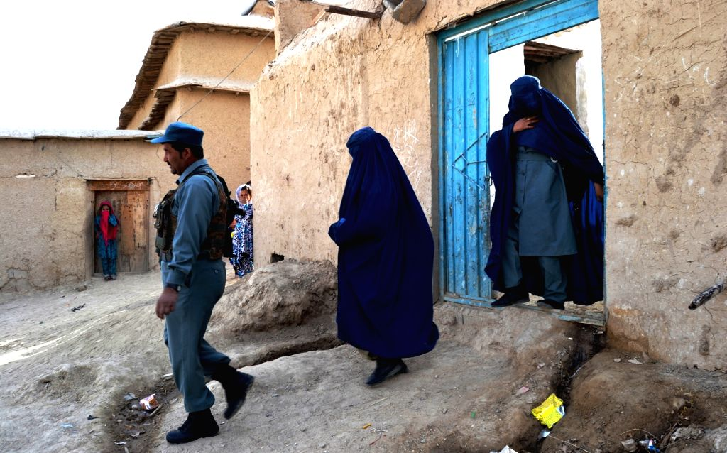 ZABUL, Nov. 29, 2016 - An Afghan polygamist policeman walks along with his two spouses who are also police officers in Qalat city, capital of southern Afghanistan's Zabul province, Nov. 21, 2016. A ...