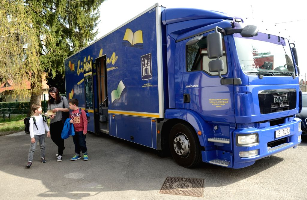 """ZAGREB, April 22, 2016 - A mother and her kids borrow books from a """"Bibliobus"""" mobile library in Gracani near Zagreb, capital of Croatia, April 6, 2016. The """"Bibliobus"""" is a ..."""