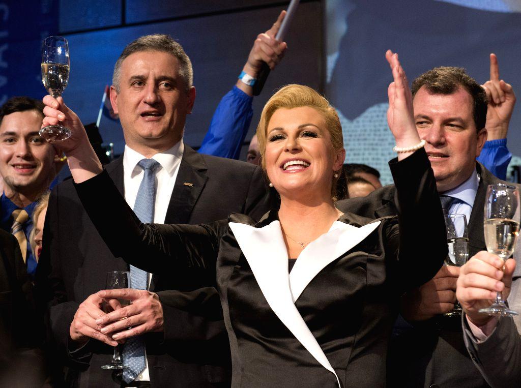 Presidential candidate Kolinda Grabar Kitarovic (front) celebrates her winning in Zagreb, capital of Croatia, Jan. 11, 2015. Kolinda Grabar Kitarovic of the ...