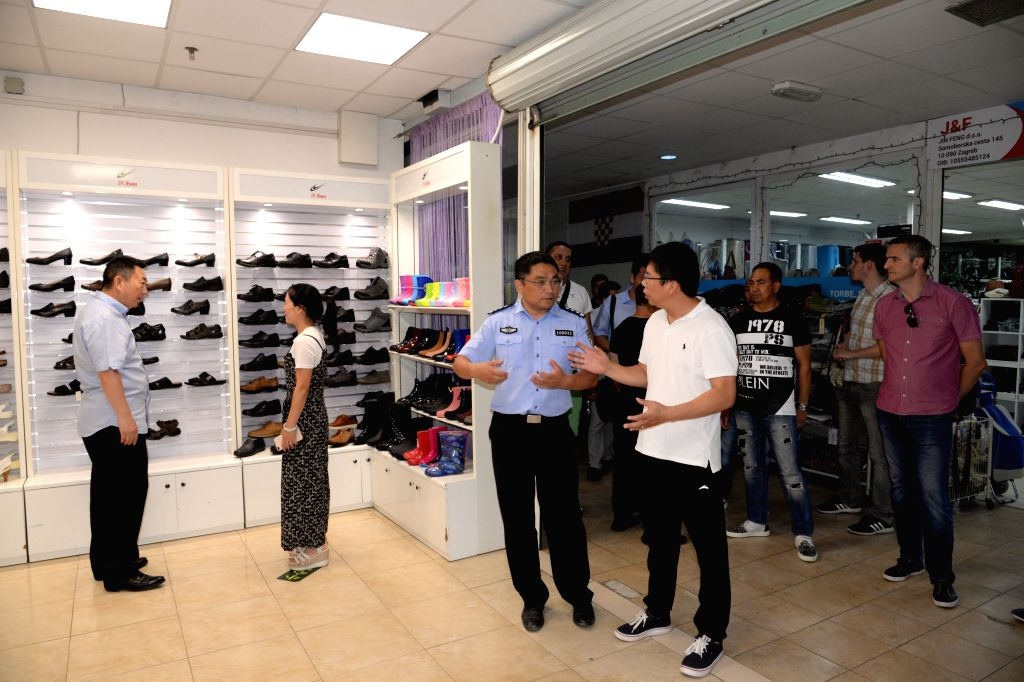 ZAGREB, July 26, 2019 - Xue Qiang (C), head of a group of Chinese police officers making joint patrol with their Croatian colleagues, visits a trade center mainly selling Chinese goods in Zagreb, ...