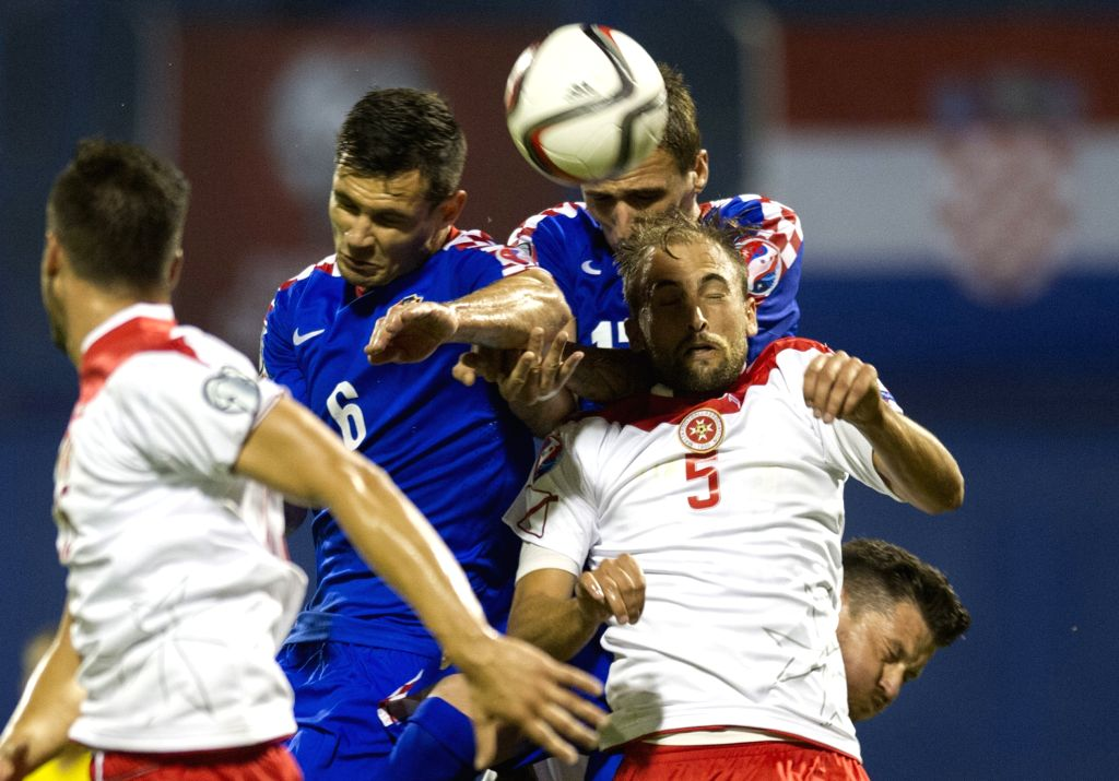 Dejan Lovren (2nd, L) of Croatia vies with Andre Aguis (1st R) of Malta during their Euro 2016 qualifying soccer match in Zagreb, Croatia, Sept. 9, 2014. Croatia ...