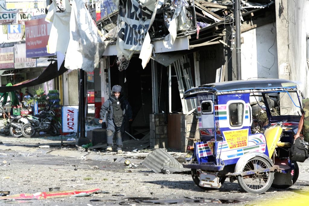 A police bomb disposal officer inspects the blast site in Zamboanga City, the Philippines, Jan. 23, 2015. At least one person was killed and 36 others ...